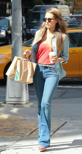 For an NYC coffee run, Alba chose wide-leg Goldsign denim, an unbuttoned chambray, and stacked Chanel sandals, accessorized with Ray-Ban clubmasters and a chain-link watch.