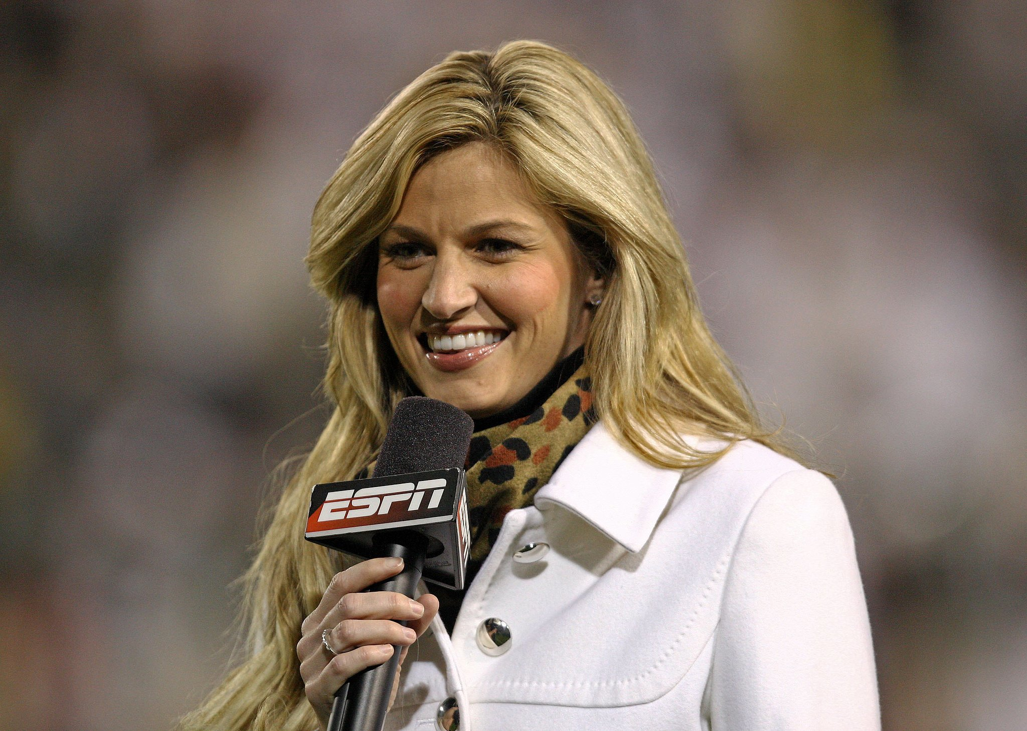 """In 2004, she started working for ESPN as a reporter for National Hockey Night. Soon, she took on sideline reporting duties for both college football and major league baseball. By 2007, she was named """"America's Sexiest Sportscaster"""" by Playboy Magazine. She had already made a name for herself in the sports world, when a peeping Tom scandal thrust her into the national spotlight in 2009. Footage of Erin naked in a hotel room was released online, and the stalker was later arrested and sentenced to 30 months in prison. Erin told Oprah that she thought her career was over because of the scandal but added, """"I also feel it's my duty to come out and show this person, you know what? I worked hard for my career and I — I got there the right way, and you're not gonna break me down."""""""