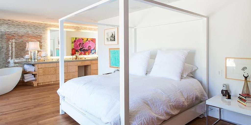 Keeping with the home's open layout, the canopy bed is neighbored with a large soak tub.  Source: Chris Cortazzo