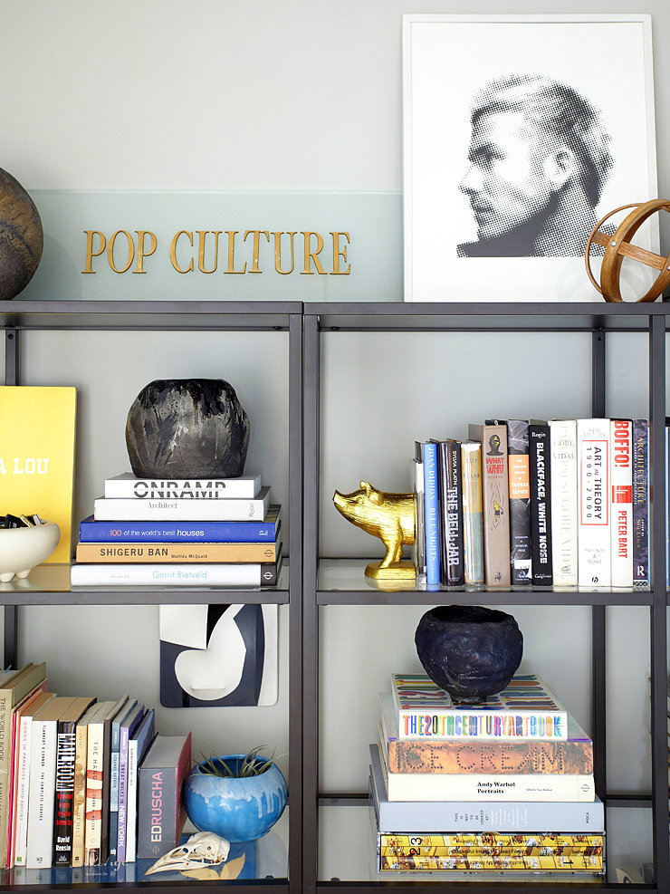 For an organized bookcase  like Orlando's, try styling books by color and arranging them both vertically and horizontally. You can also add small touches like flowers and meaningful accents throughout.  Photo by Zeke Ruelas via Homepolish