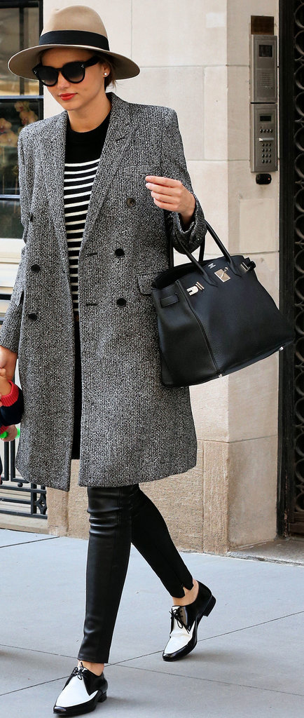 Miranda Kerr made the most of a cold Spring day with her chic black and white look. She added a checked coat, striped knit, and two-tone oxfords to a slick pair of GENETIC leather pants for a modern take on a classic look.