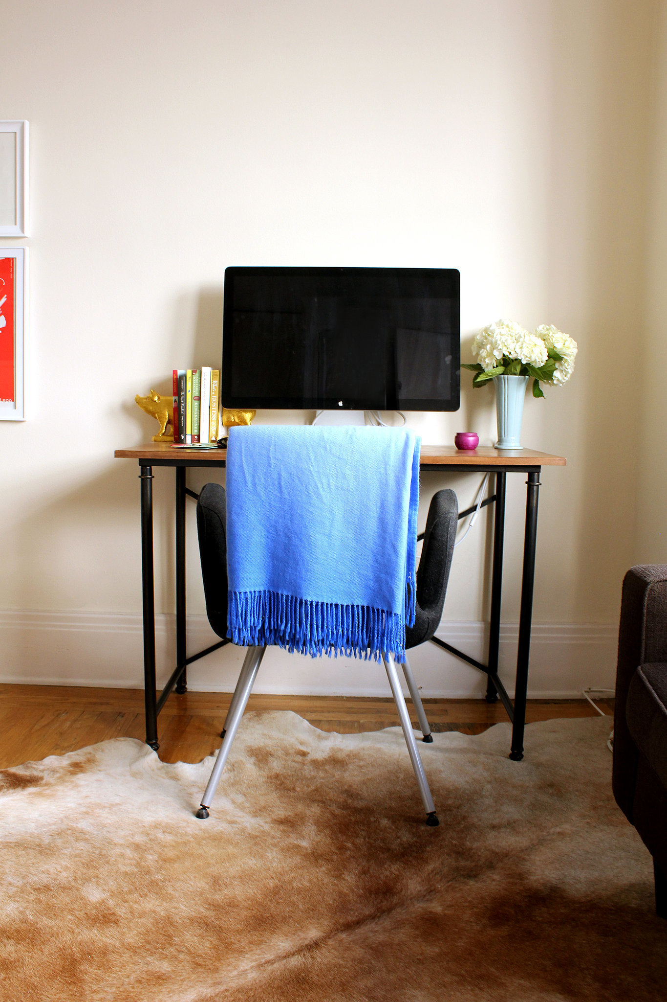 """Who says you don't have room for a work space in a studio? The wood table is not only beautiful but also practical. """"Before I buy anything, I try to make sure it serves multiple purposes,"""" says Emily. """"My desk will one day make a great console table."""""""