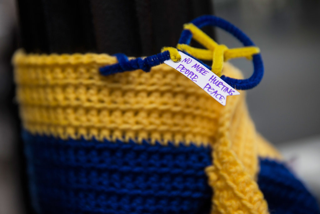 """A knitted tribute with a note — """"No more hurting people. Peace."""" — hung on a street light along the Boston Marathon course."""