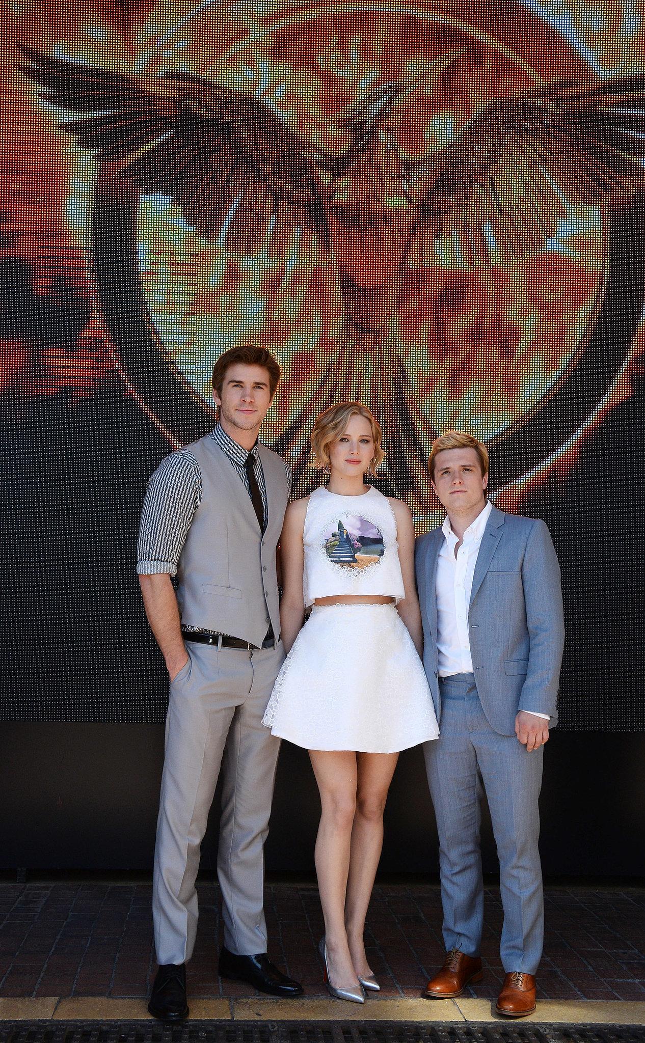 Liam Hemsworth, Jennifer Lawrence, and Josh Hutcherson stood in front of a giant Mockingjay backdrop.