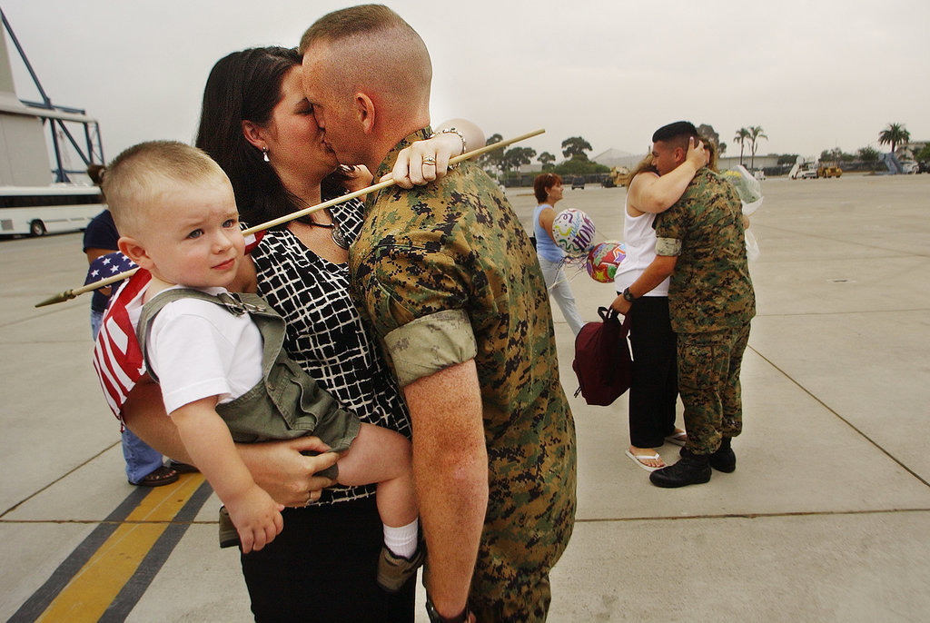 US Marine Staff Sergeant Chris Carlson kissed his wife, Kasie, as she held their 21-month-old son Ryan during the homecoming of Helicopter Squadron 466 from Iraq on July 22, 2003, at Miramar Marine Corps Air Station in San Diego. His squadron's routine six-month deployment became more than a year spent overseas due to the war in Iraq, making it one of the longest deployed units in the Marine Corps.