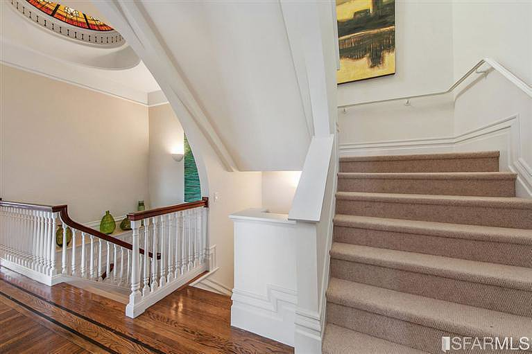 A grand staircase feels welcoming with the addition of art and soft carpeting.  Source: Coldwell Banker