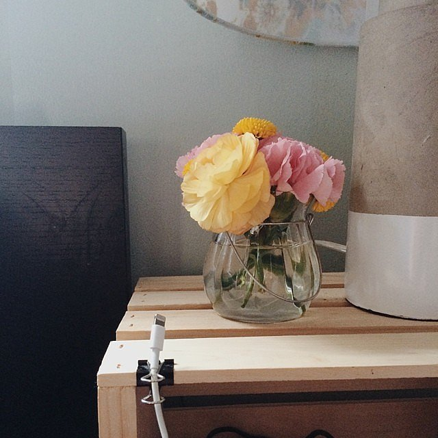 Minimalism can be stunning when styled properly. Top a bare-bones nightstand with beautiful blooms and a simple lamp for a piece of decor that draws the eye.