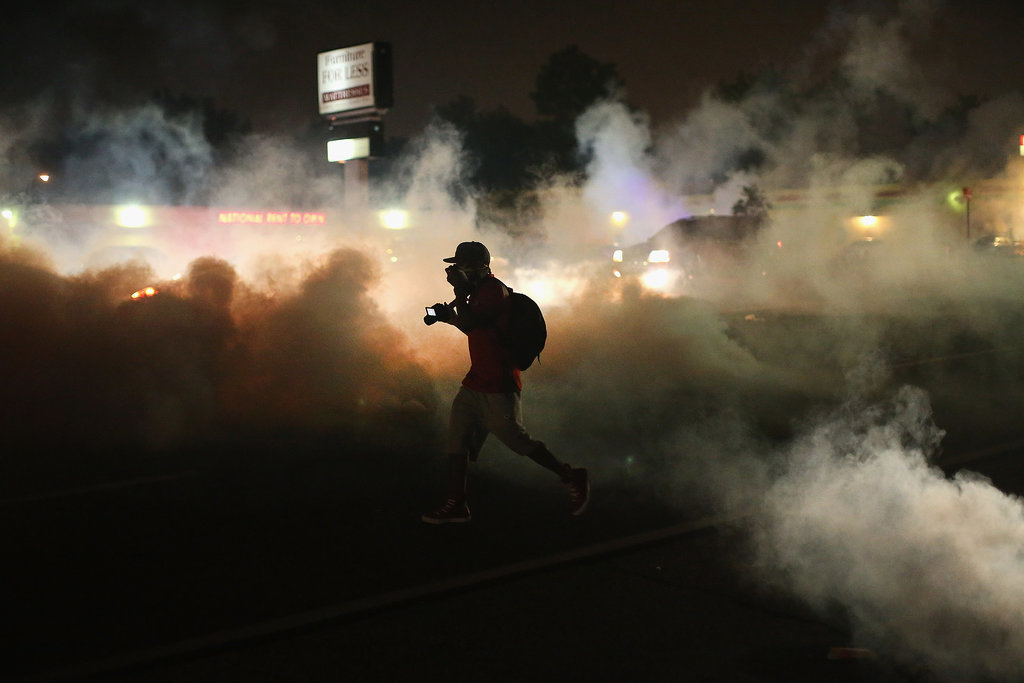 A person ran through the smoke after police launched tear gas in Ferguson, MO.