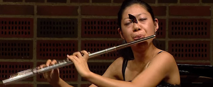 A Flutist Impressively Keeps Playing With a Butterfly on Her Face For an Entire Minute