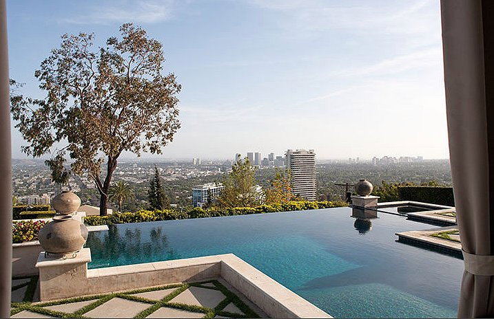the infinity edge pool gives the mansion a modern touch. Black Bedroom Furniture Sets. Home Design Ideas