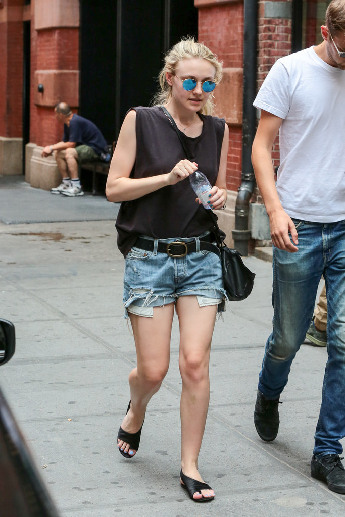 Dakota belted her cutoffs and cinched them at the waist with a belt. She completed her outfit with leather wraparound sandals.