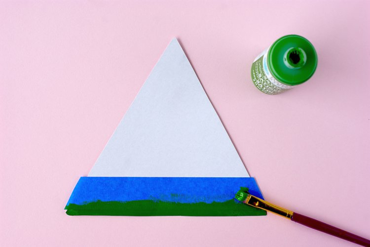 I took card stock and cut out a triangle about 6 inches on each side. Then, using painter's tape I started at the base with a dark green stripe.