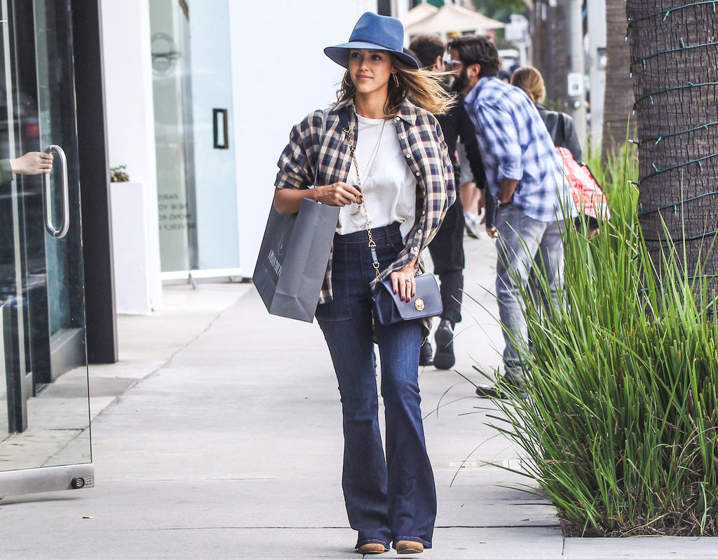 Jessica kept things casual in LA, wearing a pair of flares, a white shirt, and a plaid button-down, completing her look with a fedora.