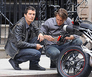 Slide Photo of Orlando Bloom Crouched Behind a Motorcycle