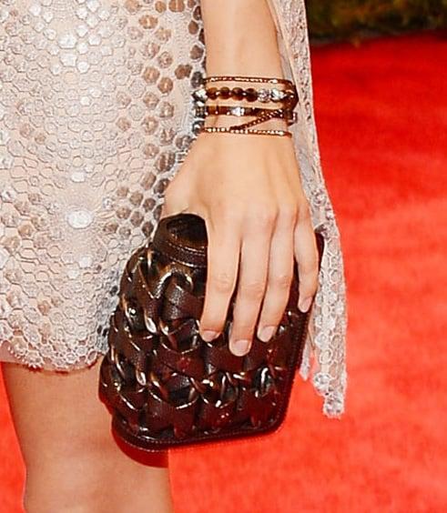 Aubrey Plaza wore skinny jeweled bangles and carried a braided clutch.