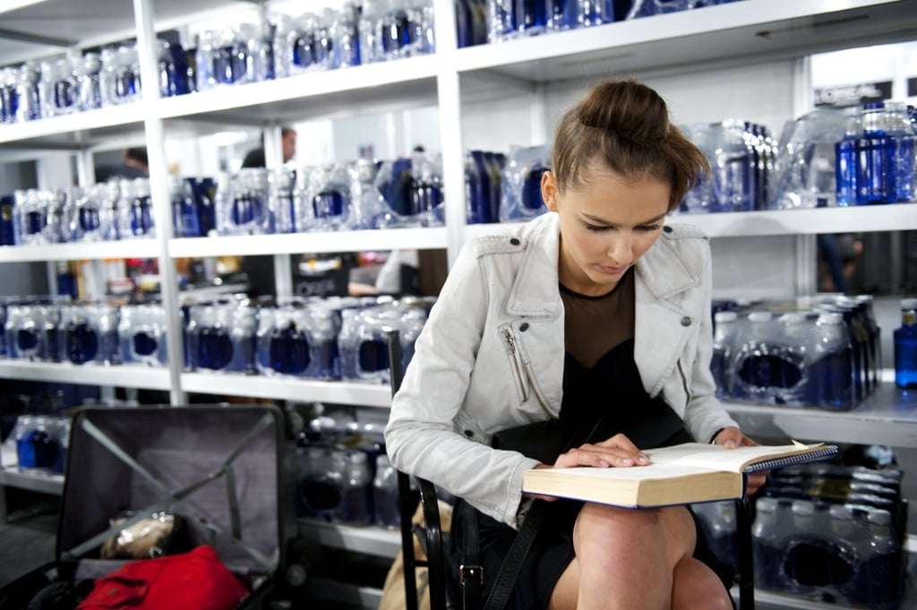 A model was into her book backstage during the Cibeles Madrid Fashion Week for Spring/Summer 2013.