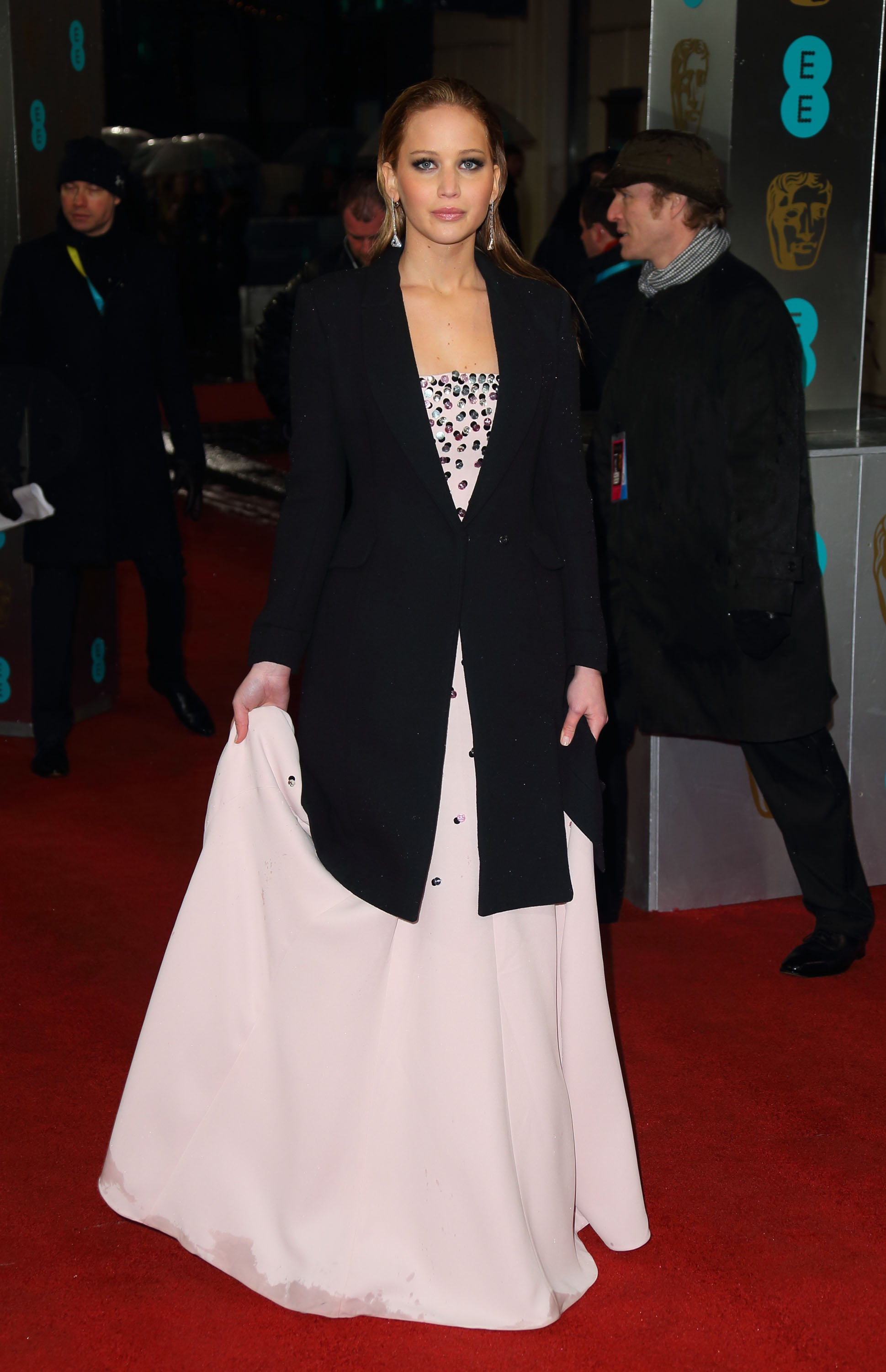Jennifer Lawrence covered up her Dior Haute Couture gown with a coat on the BAFTA red carpet.