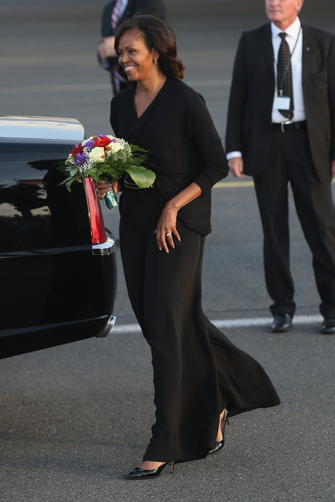 Michelle painted herself all black while in Berlin. We spied an edgy studded belt underneath her draped top.