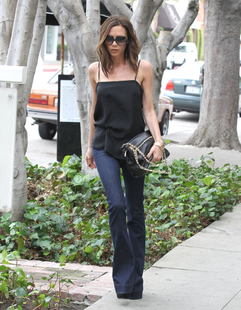 As you can see from this March 2012 snap, Victoria started her wide-leg denim streak long ago. Here she was spotted walking Melrose Avenue in LA in a black silk tank, dark-wash jeans, her signature oversize sunglasses, and a black chain-handle Victoria Beckham bag. Match these J Brand flare jeans ($324) with a black tank to get Victoria's look.