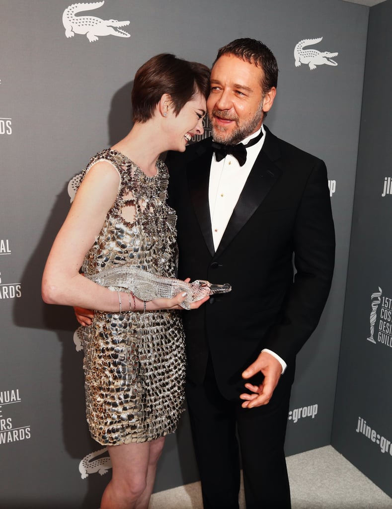 Anne Hathaway laughed with Russell Crowe after he presented her with a Lacoste spotlight award at the Costume Designers Guild Awards.
