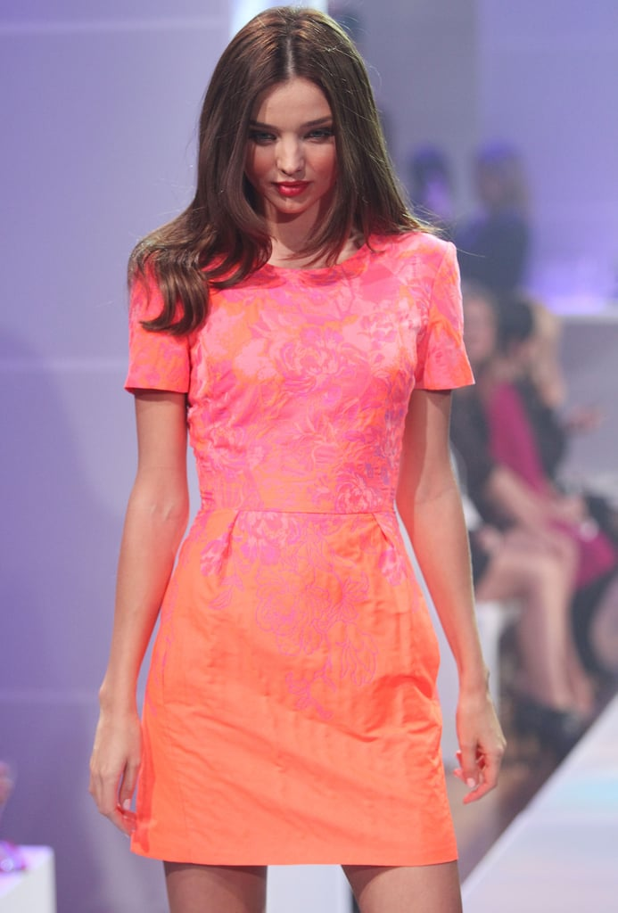 Miranda Kerr wore a pink and orange frock on the runway.