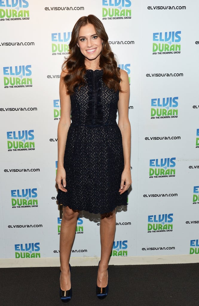 During a visit to the Elvis Duran Z100 morning show in NYC, Allison Williams stuck to her sweet aesthetic in a black sleeveless lace dress, then fancied up her feet via navy satin pumps.