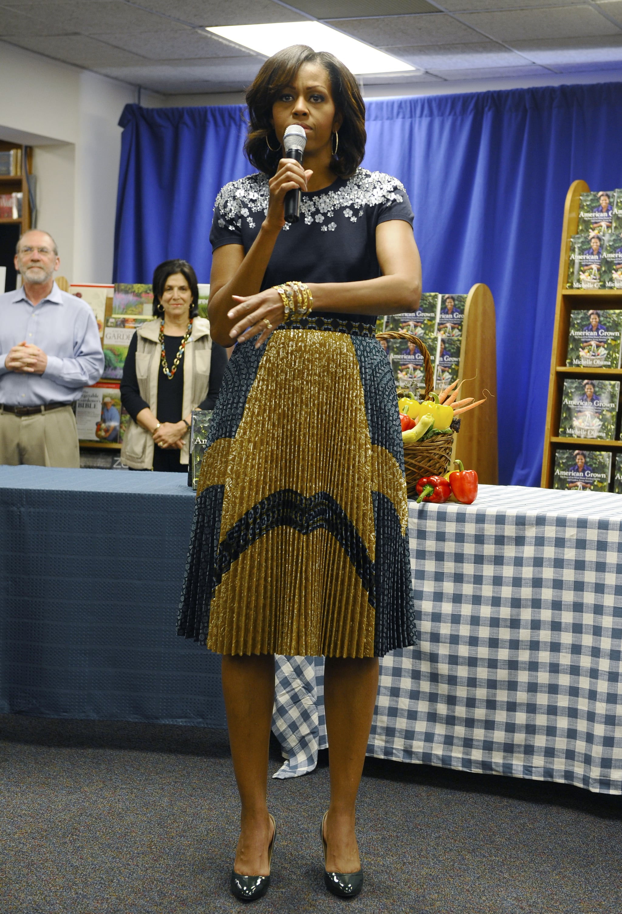 Michelle Obama paired an embellished navy top with an even more dynamic skirt on bottom. The blue and gold color pattern only elevated the crisp pleats and subtle embroidery.