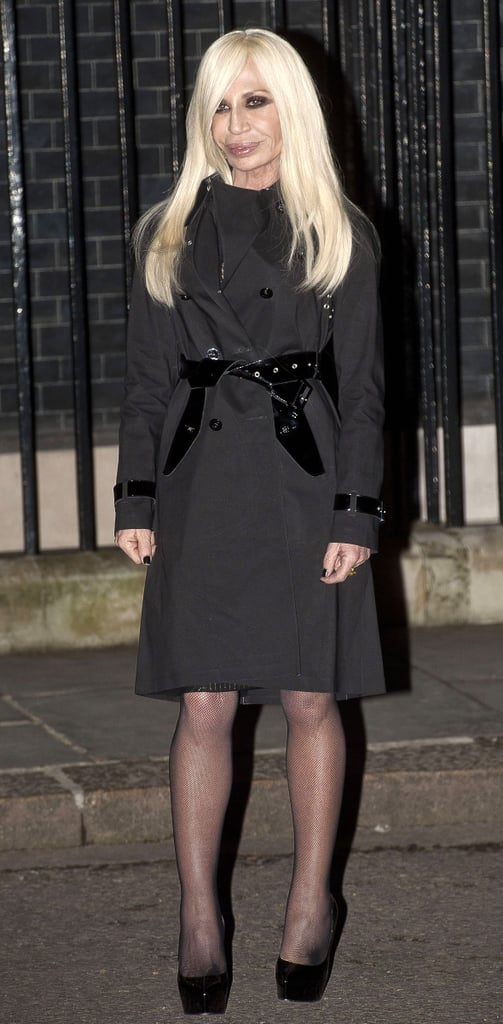 Donatella Versace covered up in a black trench coat and black platform pumps while arriving at 10 Downing Street during London Fashion Week.