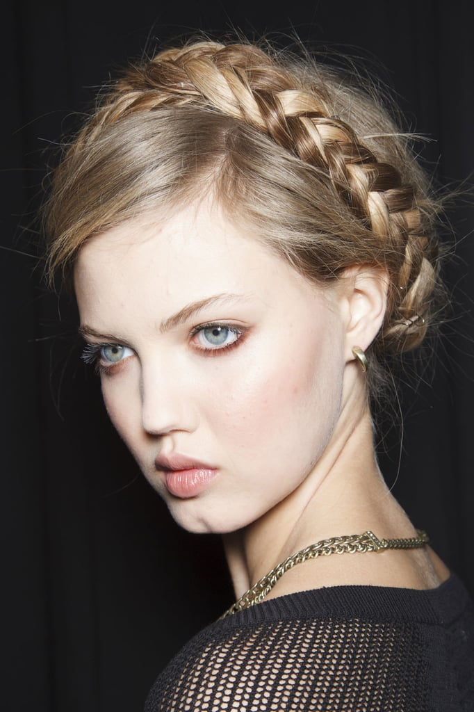 """""""The trick to parting your hair for milkmaid braids is to keep the part messy. I use the end of my comb to make a zigzag all the way to the back of the head.""""  — Hairstylist Jeanie Syfu at Rebecca Minkoff (as modeled by Lindsey Wixson, pictured)"""