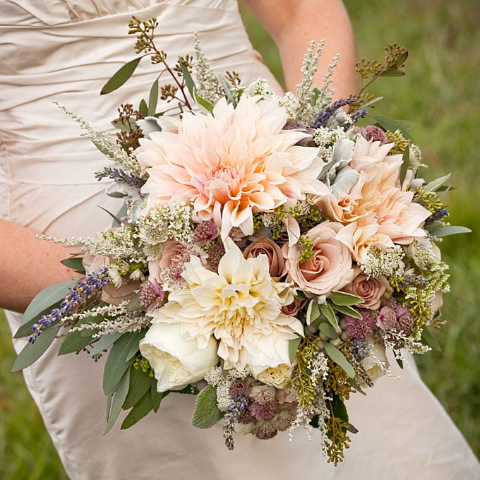 "A Rustic-Romantic Bouquet of Dahlias and Roses Tying the knot outdoors? Consider a textural arrangement that complements your surroundings. Holly Chapple of Virginia-based Holly Heider Chapple Flowers designed this bouquet for a bride getting married on a vineyard and celebrating in a barn. ""The entire wedding had an organic aesthetic. The bride's palette was muted pinks and dusty lavender tones,"" says Chapple. We love the from-nature look here, achieved by surrounding extra-large café au lait dahlias with cabbage, amnesia, and quicksand roses, field flowers, silver-sage foliage, and lavender. Browse more pink wedding flower ideas. Related: Wedding Etiquette Tips: The Bridal Party Source: Genevieve Leiper Photography"