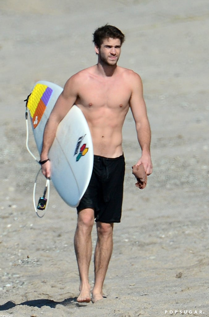 Liam Hemsworth carried his surfboard on the beach in Costa Rica in January 2013.