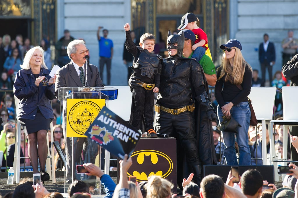 Batkid held up his hand, celebrating with his family.