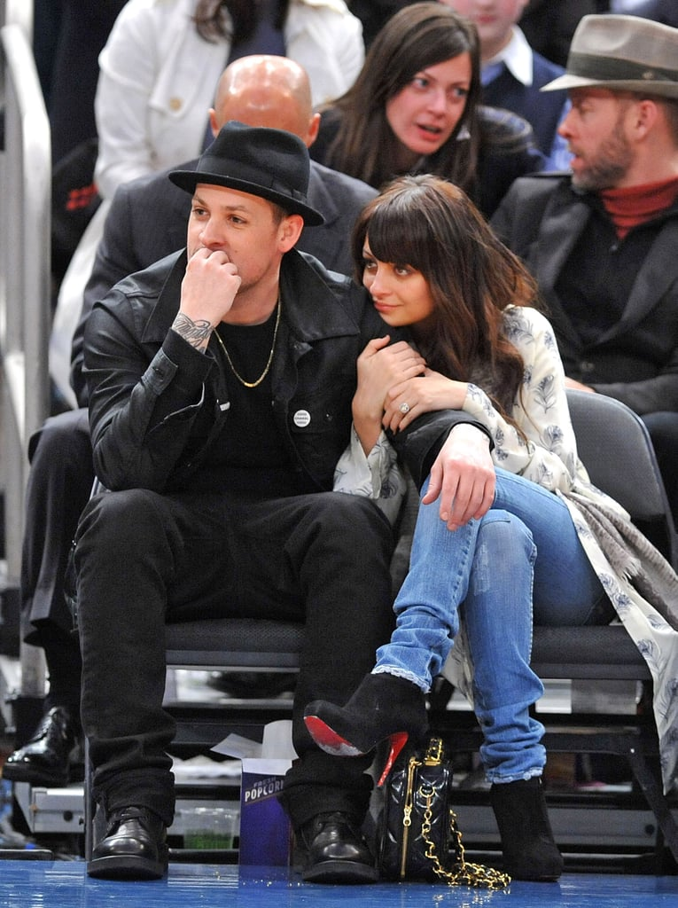 Nicole Richie held onto Joel Madden's arm during a basketball game at Madison Square Garden in 2010.