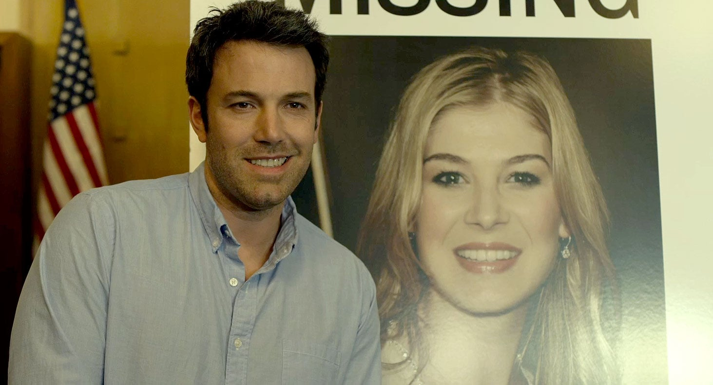 "Nick (Ben Affleck) makes a mistake when he smiles smarmily in front of his wife's ""Missing"" poster."