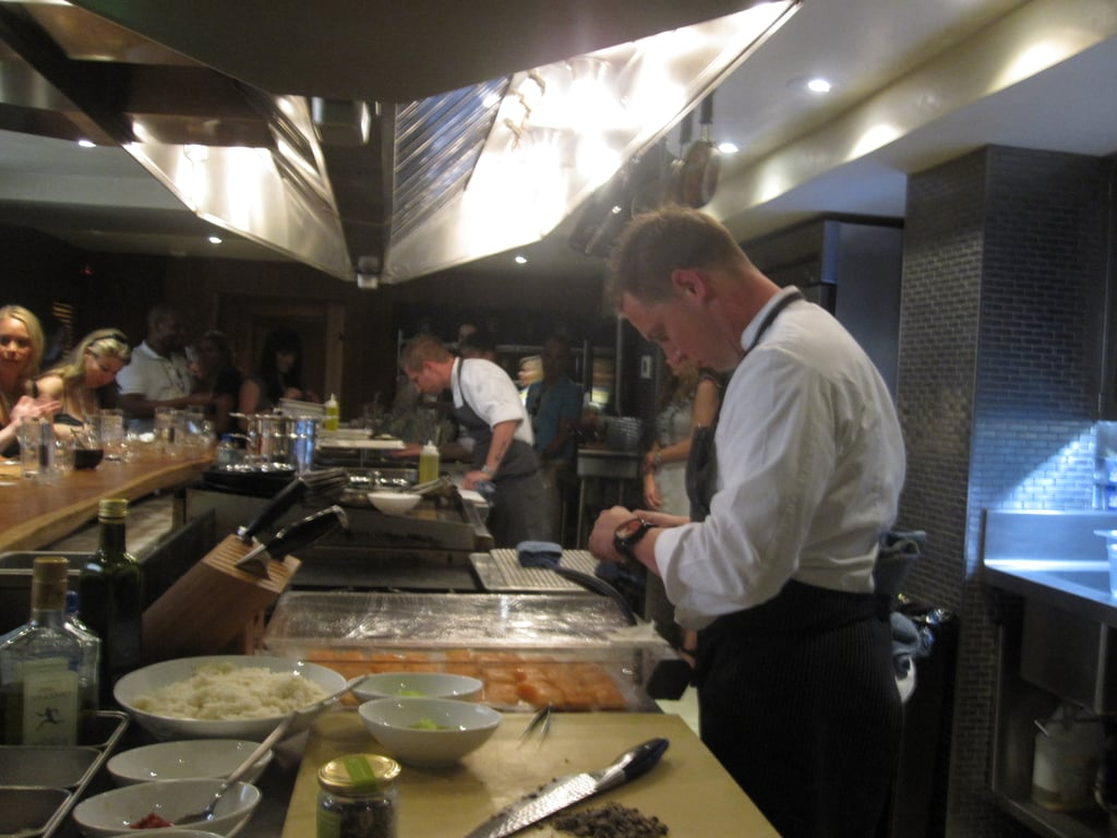 Michael, at the far end, prepares the plates for the first course, while Bryan sets up the smoking gun.