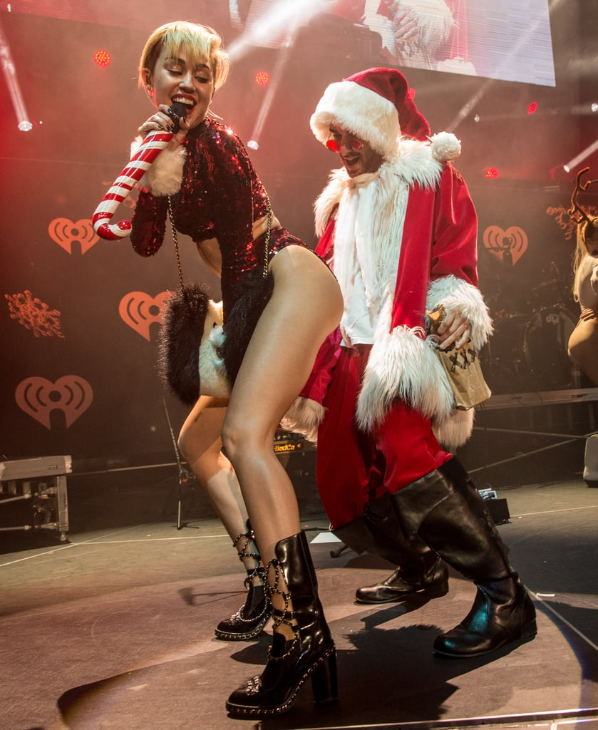 After a series of uncharacteristically tame performances, Miley got flirty on stage once again at the KIIS FM's Jingle Ball concert in LA on Dec. 6. While singing into a candy-cane microphone, scantily-clad Miley twerked, stuck out her tongue, and danced with a friend dressed as Santa Claus.