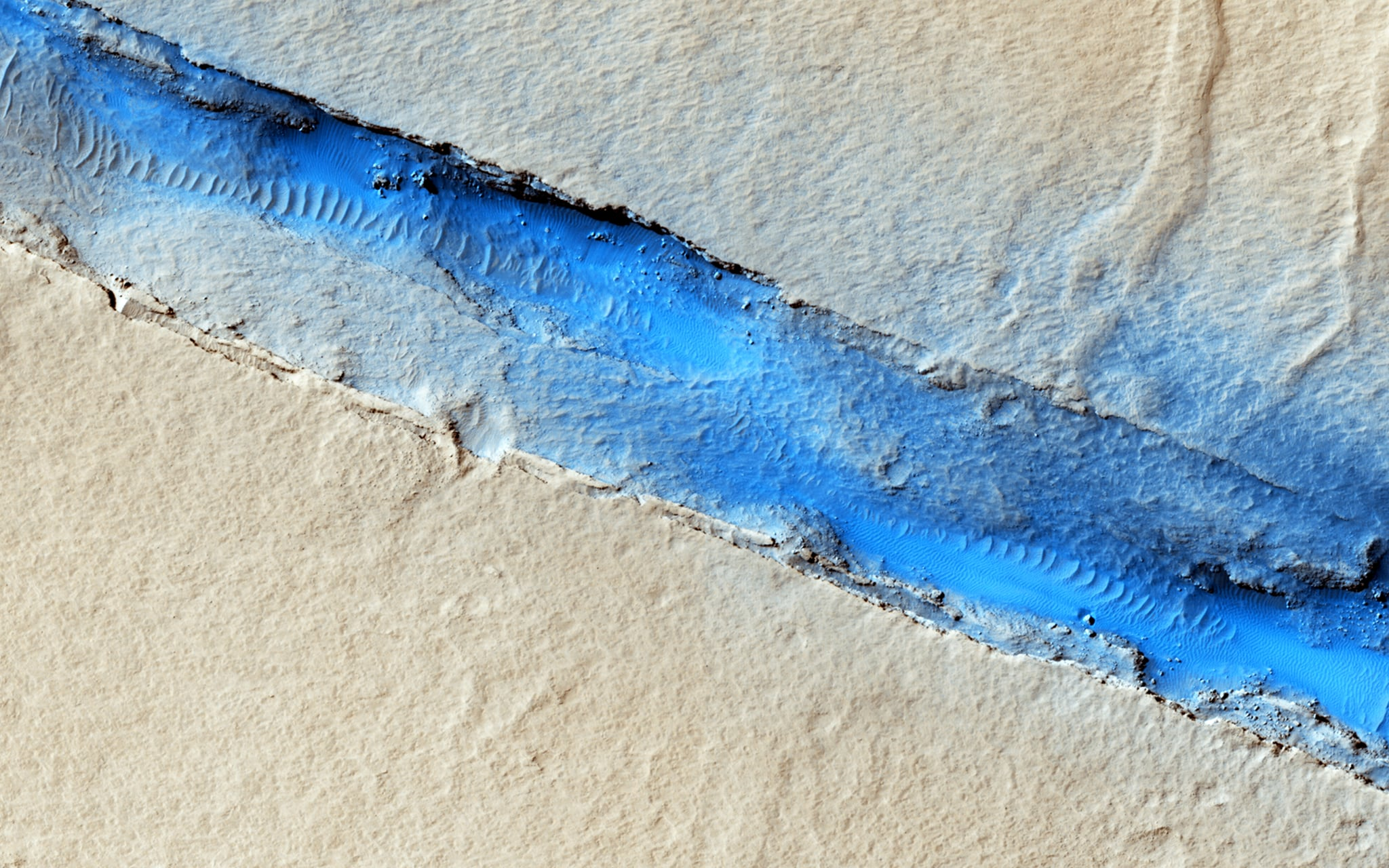 """""""The linearity of the volcanic vent shown in this HiRISE image, in conjunction with evidence of lava flow from the vent, suggests control by combined volcano-tectonic processes."""" Source: NASA/JPL/University of Arizona"""