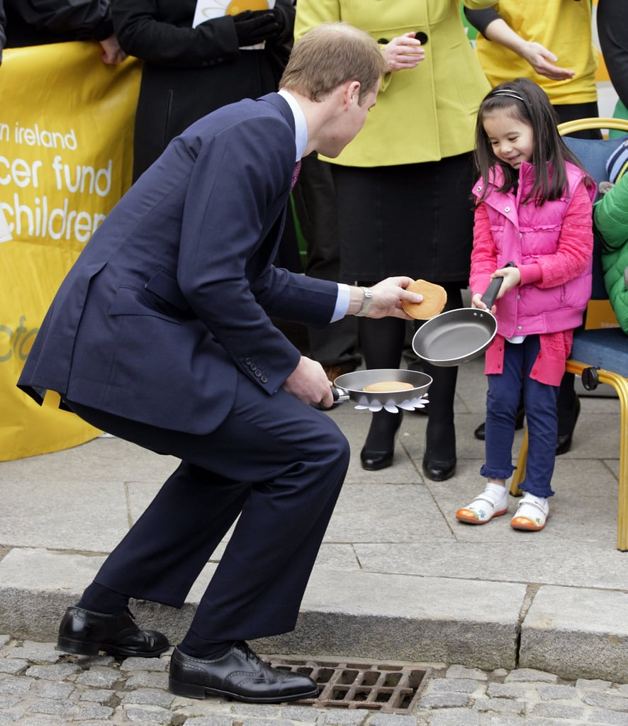 """How's this for adorable? During a """"pancake tossing"""" event at Belfast City Hall in March 2011, a little girl dropped hers — and William cutely picked it up for her."""