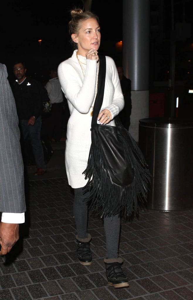 Kate Hudson's boho style made for a comfortable on-flight outfit. She kept her look simple, wearing a long sweater dress over leggings and going with stylish snow boots instead of heels. And there was no rolling trolley for this girl; she carried her essentials in an oversize fringed bag.