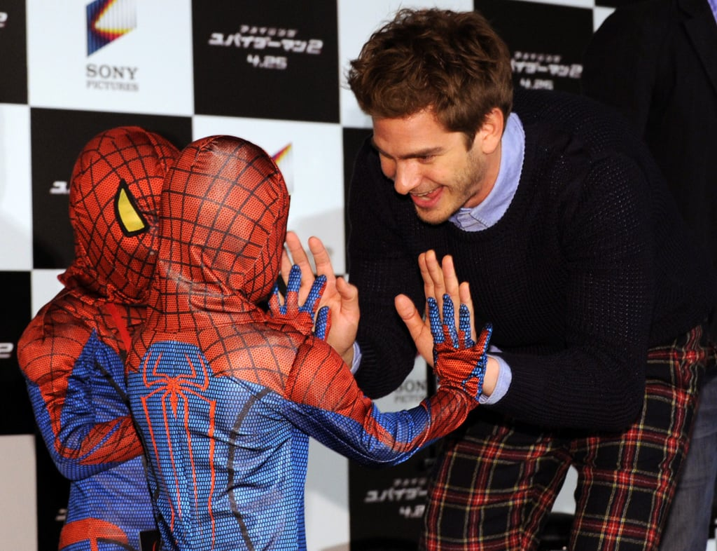 Andrew high-fived two tiny Spider-Man fans.