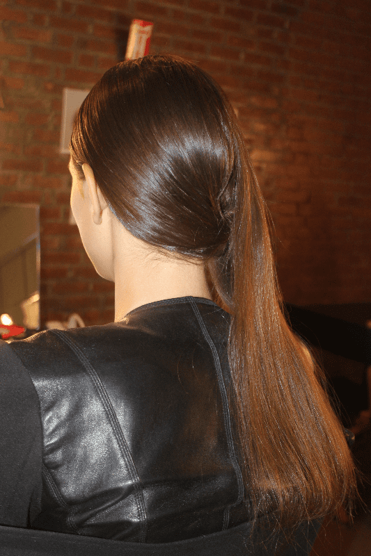 To achieve this look, stylists first created a side part in the front, and used Kiehl's Clean Hold Gel ($16) and Serge Normant Hair Spray ($25) for a high-gloss effect. In the back, hair was gathered into an off-center bun, where a section of hair reserved from the side was used to cover and fill it in.