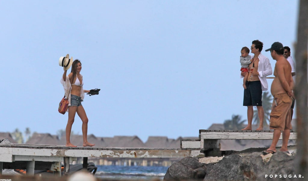 Miranda Kerr gave a wave with her hat while husband Orlando Bloom and baby Flynn looked on in Bora Bora.