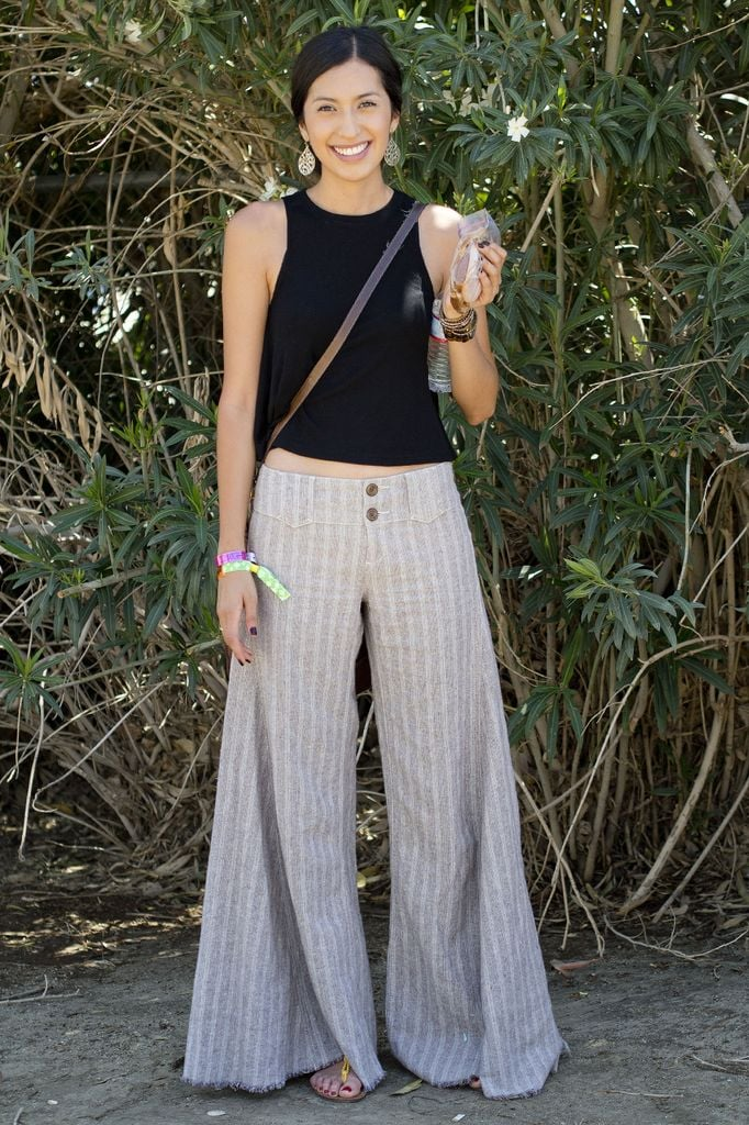 A festival attendee showed off her airy and effortless style in a pair of flowy striped pants and a simple black tank.