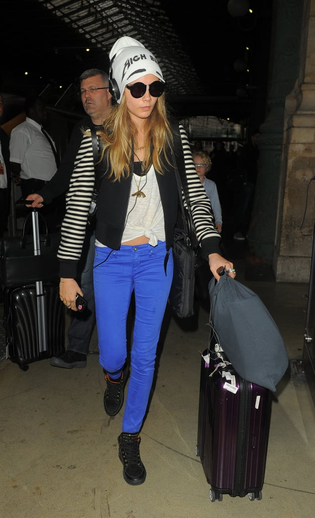 Cara Delevingne could wear a sack and still look amazing, but colour-pop denim and a cool-girl beanie is a much better airport outfit.