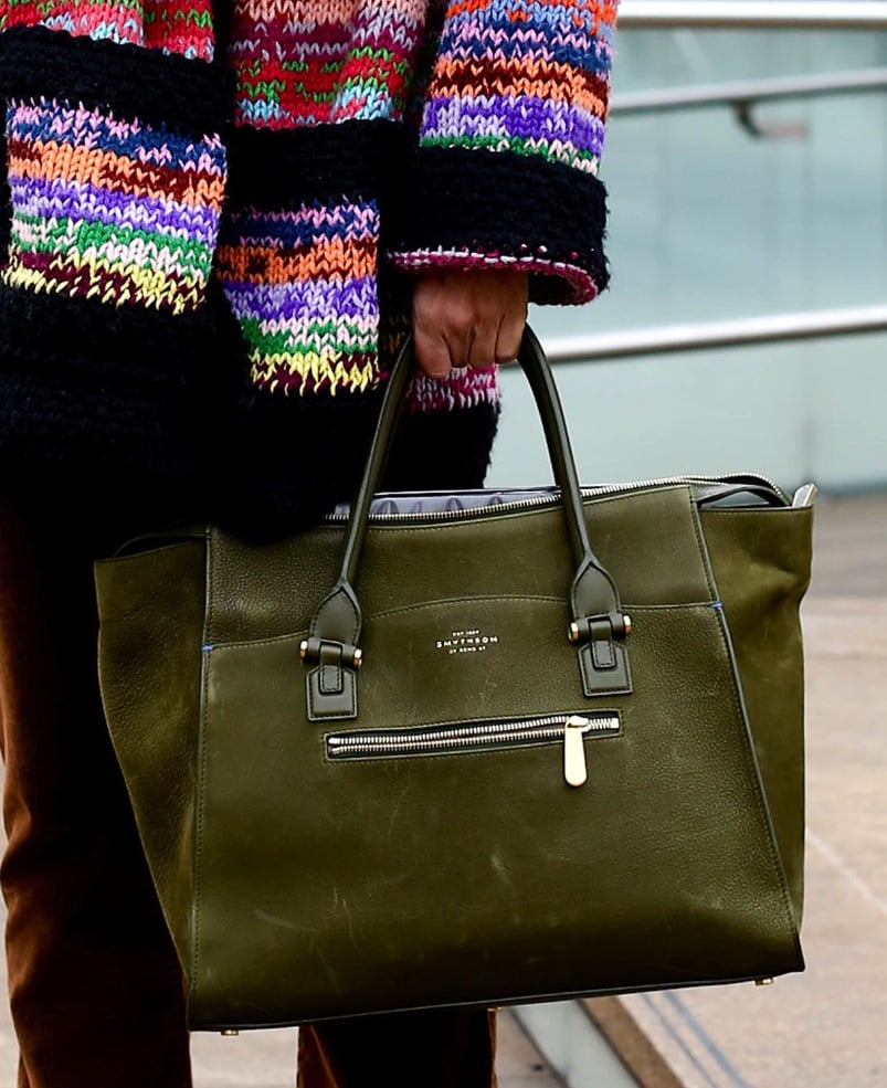 A classic forest green Smythson satchel tempers a multicolored knit.