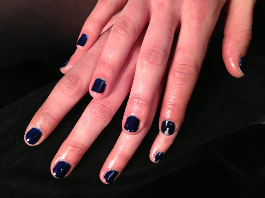 """There were three different nail looks created by Katie Hughes for Butter London. """"The inspiration was a mix of tomboys and a little rock 'n' roll,"""" she said. And each of the three looks corresponded with the three themes from the collection. Wallis, a glittery olive, went with the sexier, more ladylike clothes. Stag Do, a dark turquoise, was paired with the more tomboyish looks, while Royal Navy complemented the edgier ensembles. To amp up the navy-blue nails, a small silver stud was painted on random accent nails."""