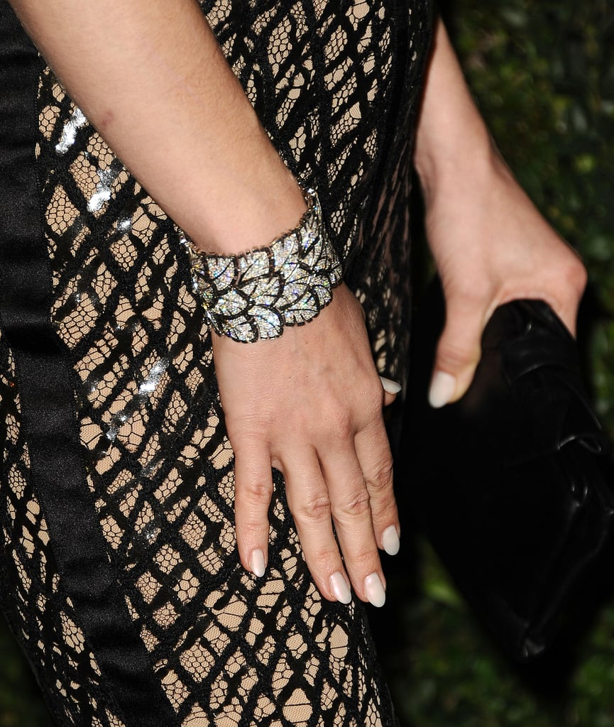 """Upon closer review, you'll see just how intricate the texture is on January Jones's black """"webbed"""" pants. Lest we forget, she added a black-and-white Chanel diamond cuff into the mix too."""