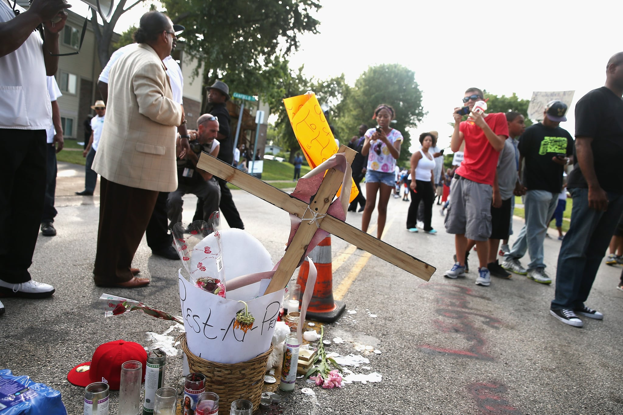 A cross, flowers, and candles were placed at the spot where Michael Brown was killed.