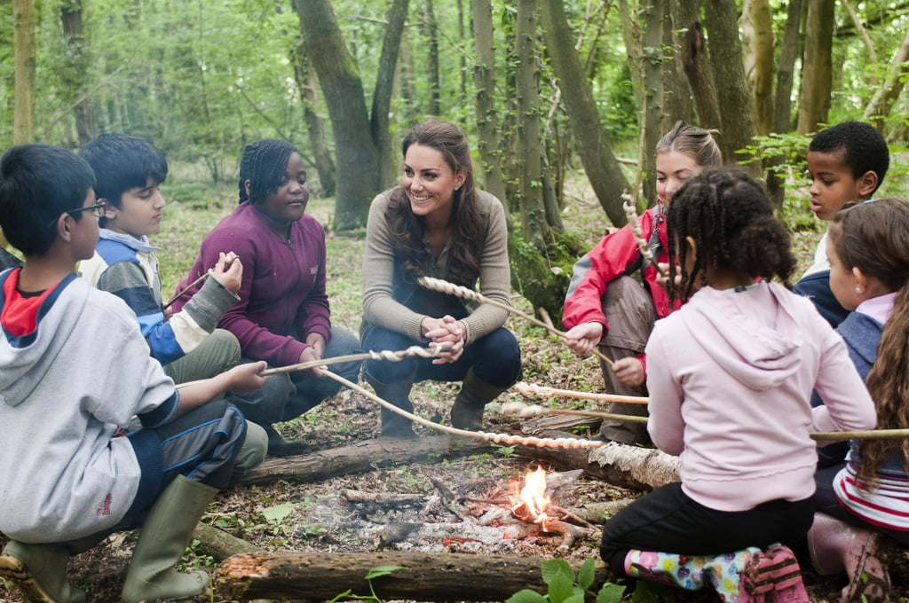 Kate Middleton sat around a campfire with children from Expanding Horizons primary school outdoor camp.