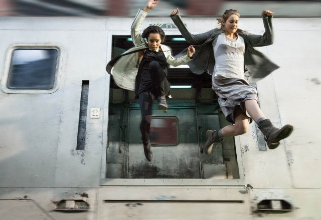 Christina and Tris jump out of a train as Dauntless initiates.